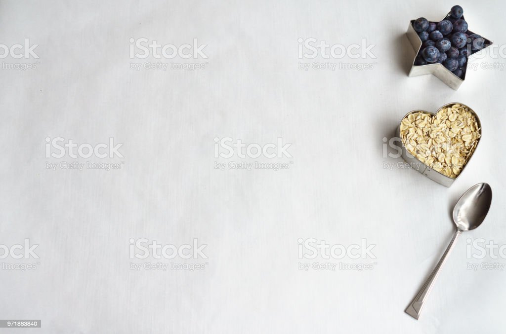Organic Oats, Organic Blueberries, a Spoon and Whitespace stock photo