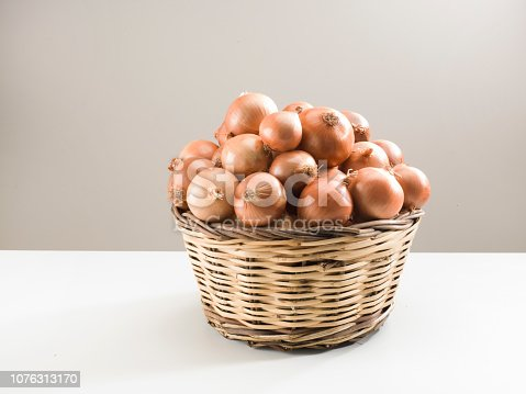 Organic Onions in Wicker basket on white and brown background.