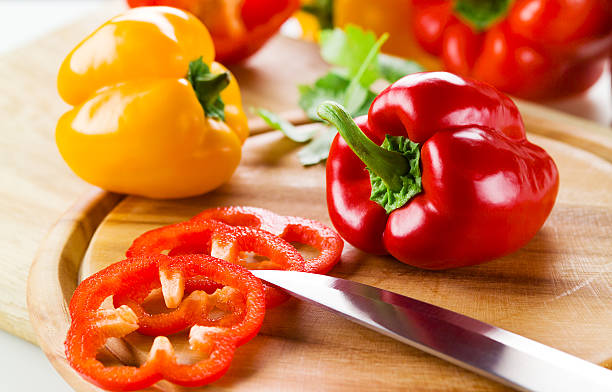 Organic paprika peppers with slice over wooden table stock photo