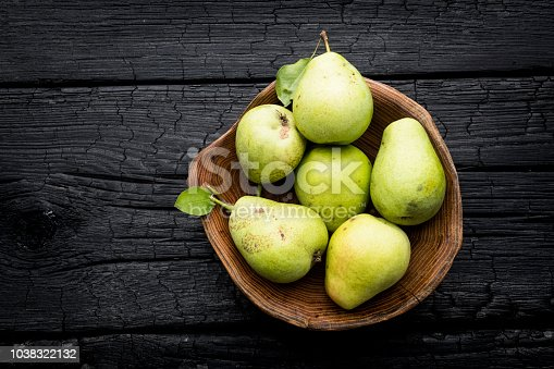 Pears in wooden bowl on dark wooden background