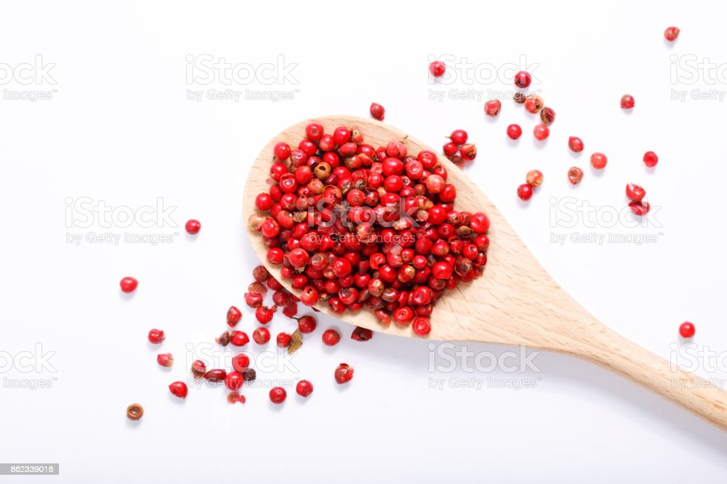 Organic Pink Peppercorn in wooden spoon on white background with copy space stock photo