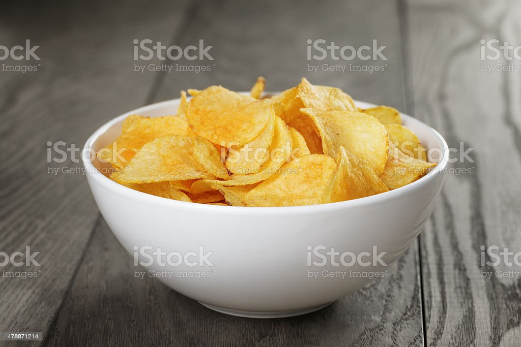 organic potato chips in white bowl on wood table stock photo
