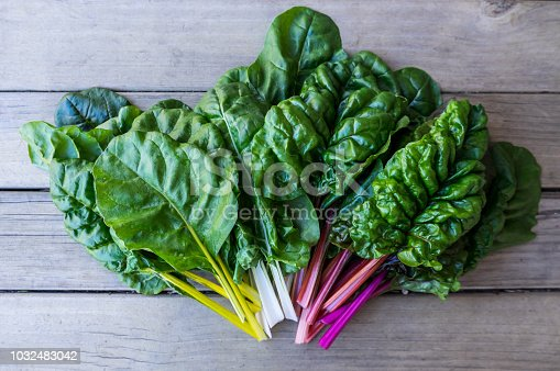Organic rainbow chard: spray-free leafy greens in fan arrangement isolated on white background arrangement on dark rustic wooden background