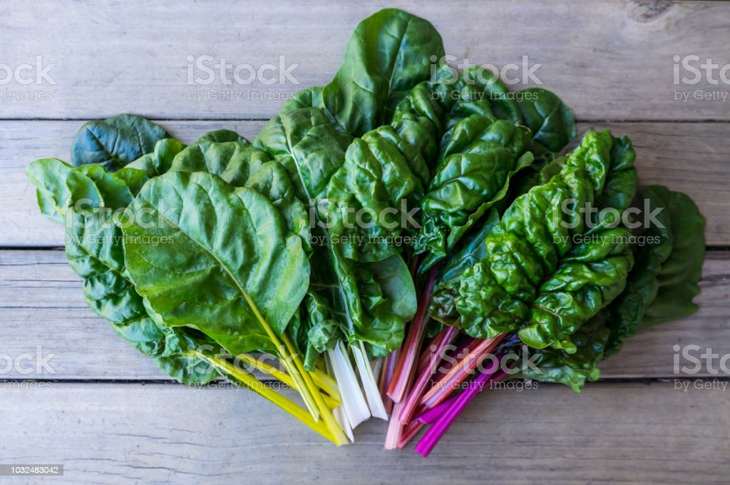 Organic rainbow chard: spray-free leafy greens in fan arrangement on rustic wooden background stock photo