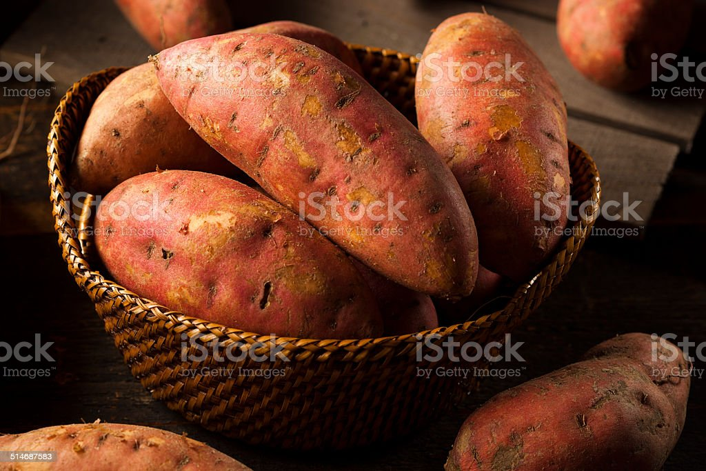 Organic Raw Sweet Potatoes Organic Raw Sweet Potatoes on a Background Food Stock Photo