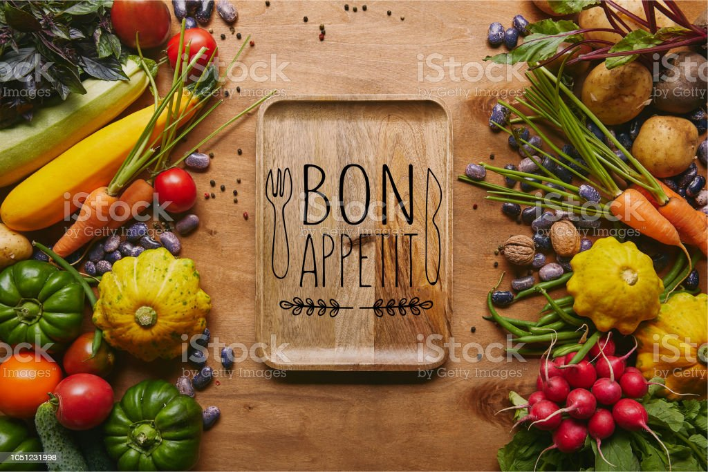 Organic raw vegetables and tray with 'bon appetit' lettering on wooden table stock photo