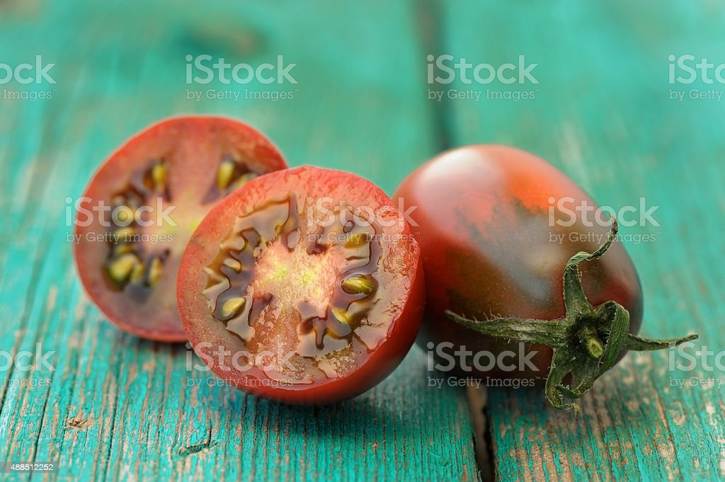 Organic red and black tomatoes cut on old turquoise table stock photo