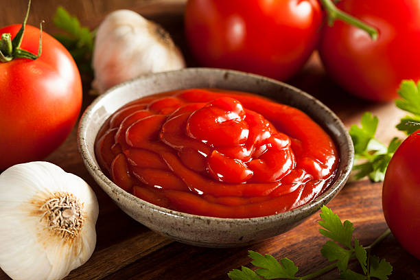 Organic Red Tomato Ketchup Organic Red Tomato Ketchup in a Bowl ketchup stock pictures, royalty-free photos & images