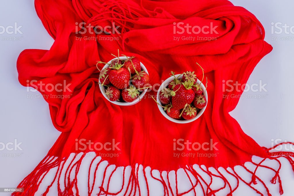 Organic ripe strawberry in white porcelain pots on a red and white background royalty-free stock photo