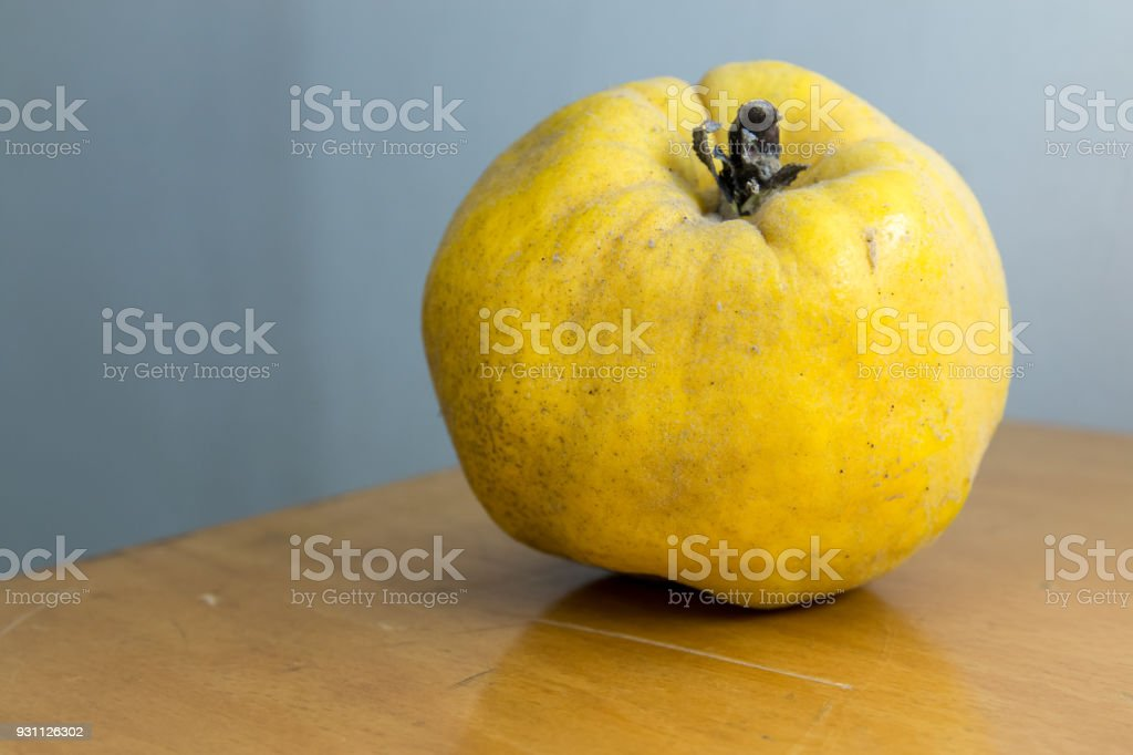 Organic Ripe yellow quince fruit on wooden table. stock photo