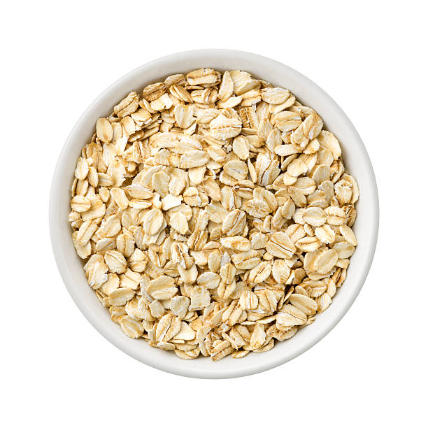 Organic Rolled Oats in a ceramic bowl Overhead View of Organic Rolled Oats in a ceramic bowl. Rich in fiber and nutrition. The image is a cut out, isolated on a white background, with a clipping path. oatmeal stock pictures, royalty-free photos & images