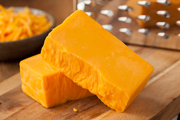 Organic Sharp Cheddar Cheese Organic Sharp Cheddar Cheese on a Cutting Board cheddar cheese stock pictures, royalty-free photos & images