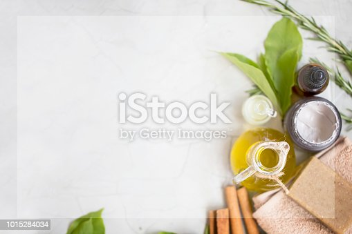 istock Organic skincare products flatlay with copy space, face oil bottle, olive oil and clay mask, natural soap on towel, top view on concrete background 1015284034
