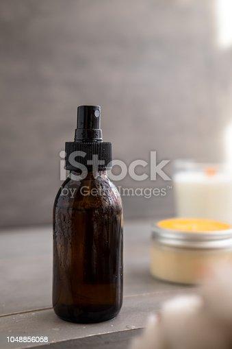 1042453716 istock photo Organic spa cosmetics in brown glass bottles 1048856058