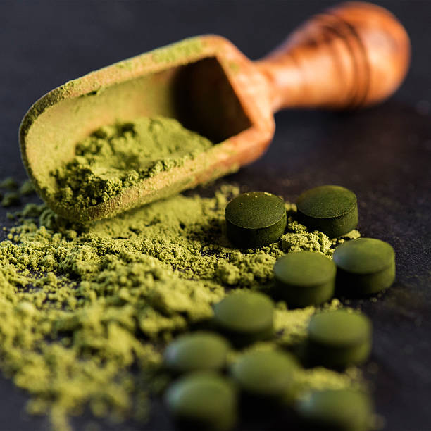 Organic Spirulina Powder and Tablets Organic spirulina powder and tablets shot on a slate  chlorophyll stock pictures, royalty-free photos & images