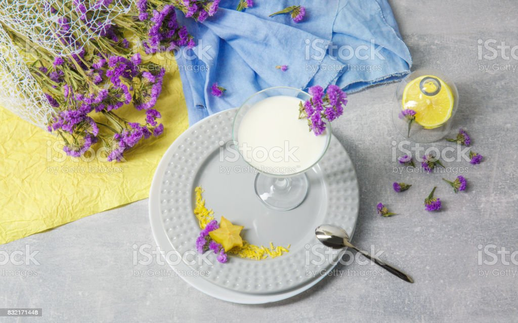 Organic sweet milkshake. A glass of cocktail with fruits on a table background. Decorative flowers, lemon and fabric. stock photo