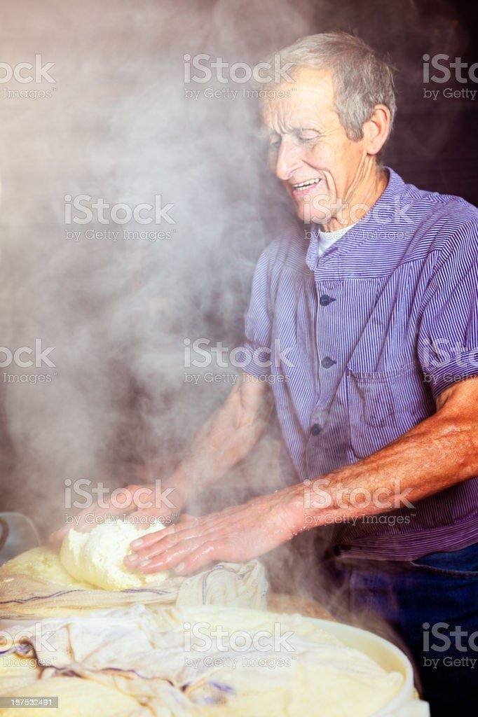 Organic Swiss Cheese Maker testing the Curd stock photo