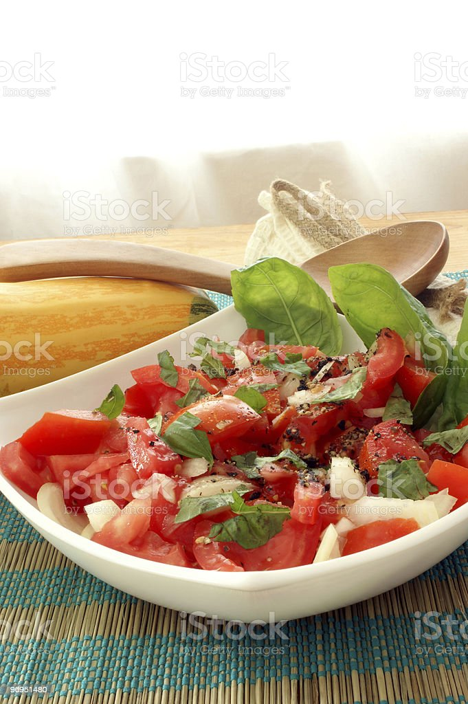 organic tomato salad in bowl with onion and basil royalty-free stock photo