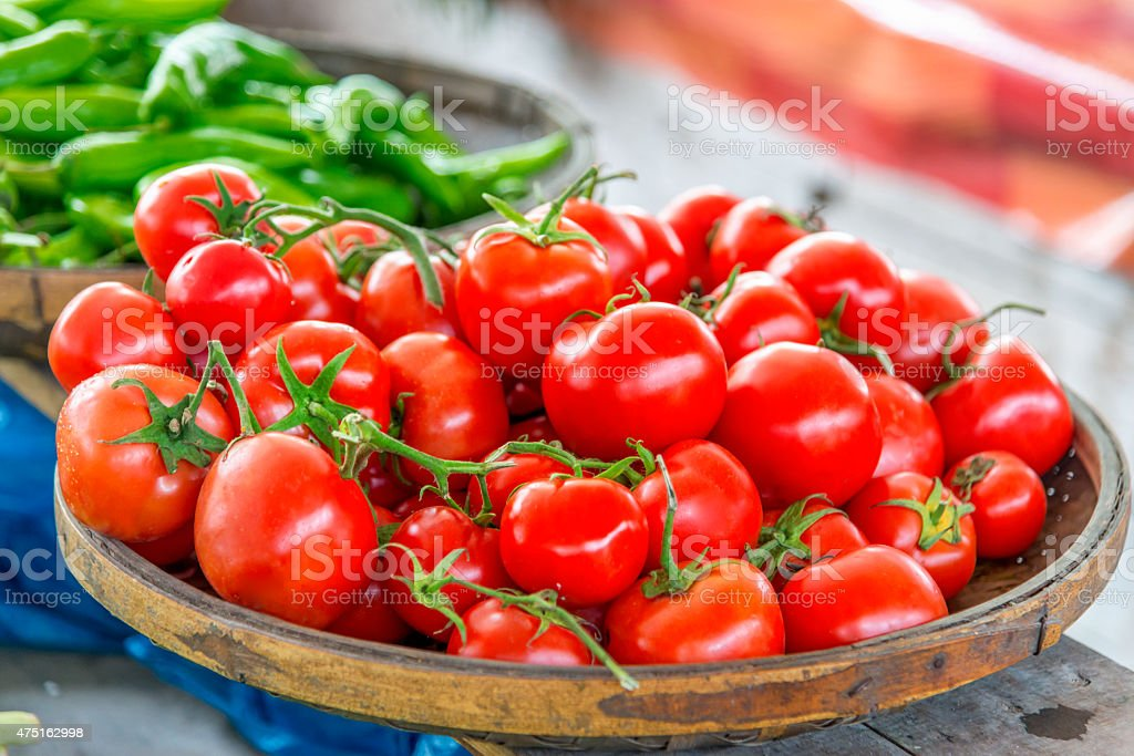 Organic Tomatoes in basket, market scene stock photo
