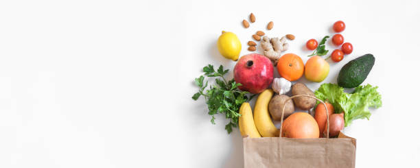 Organic vegan food Healthy food background. Healthy vegan vegetarian food in paper bag vegetables and fruits on white, copy space, banner. Shopping food supermarket and clean vegan eating concept. fruit stock pictures, royalty-free photos & images