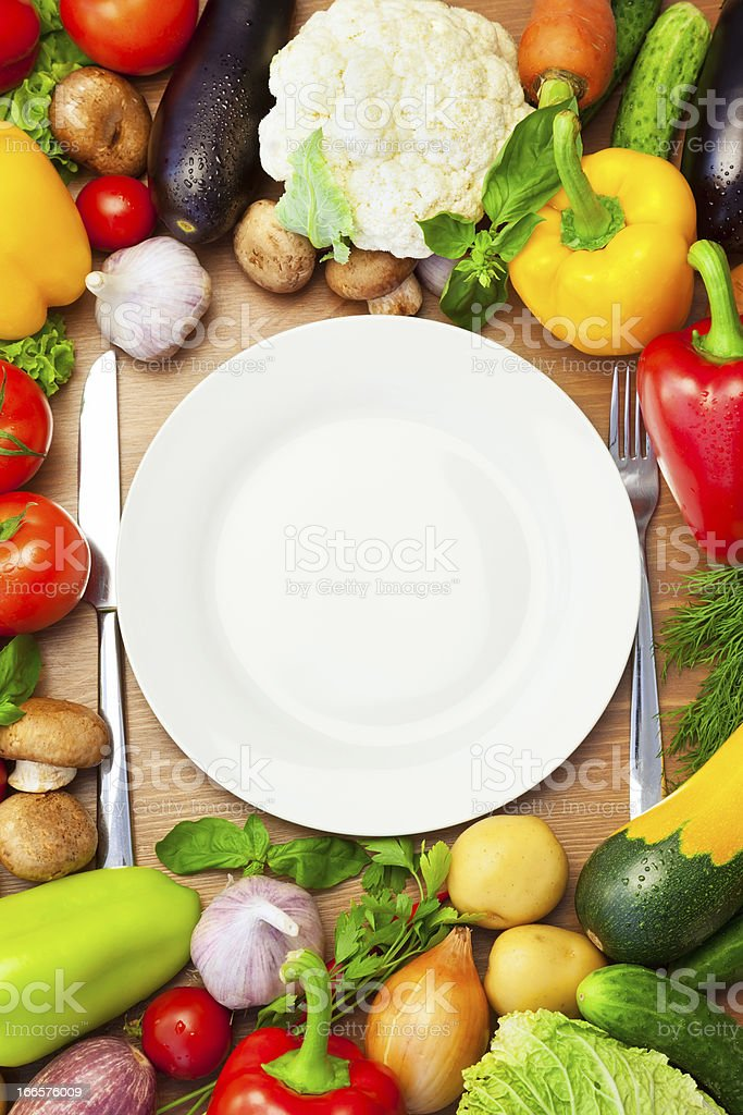 Organic Vegetables Around White Plate with Knife and Fork royalty-free stock photo