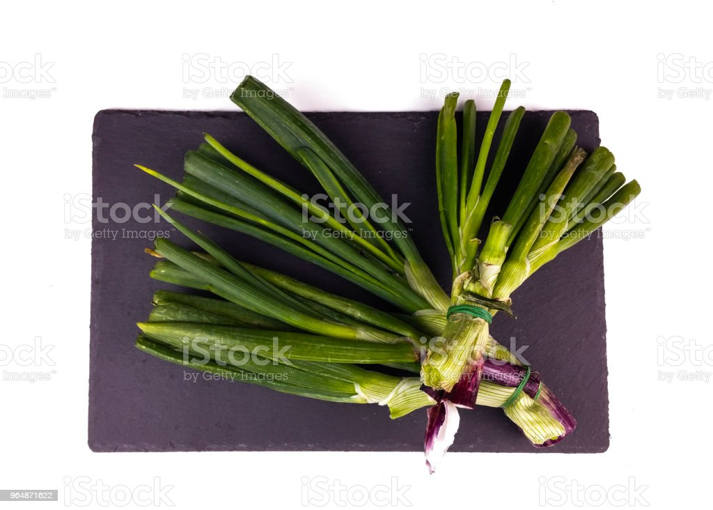 Organic waste of onion scraps on slate plate and white background - top view royalty-free stock photo