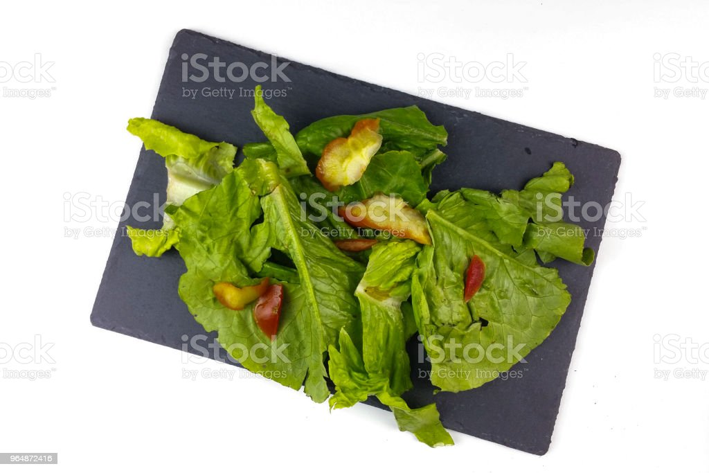 Organic waste of tomatoes, onion and lettuce scraps on slate plate and white background - top view royalty-free stock photo