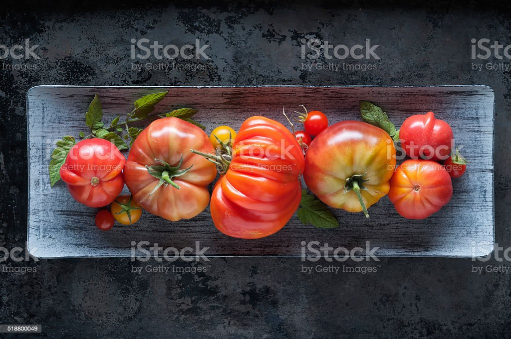 Organically Homegrown Heirloom Tomatoes in Rustic Platter stock photo