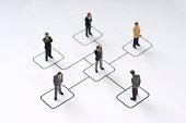 6 Businessmen figurines standing on organization chart