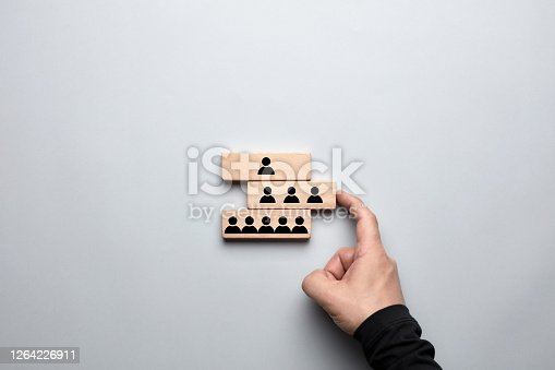 Organizational hierarchy or human resources strategy concept. Male hand pushing the wooden block with middle level employee or managers and completing the corporate structure.