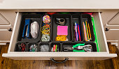 istock Organized desk drawer with office supplies in bins 1298201425