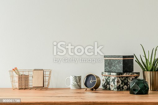 Organized table top with floral boxes, mug, clock and metal box on empty wall