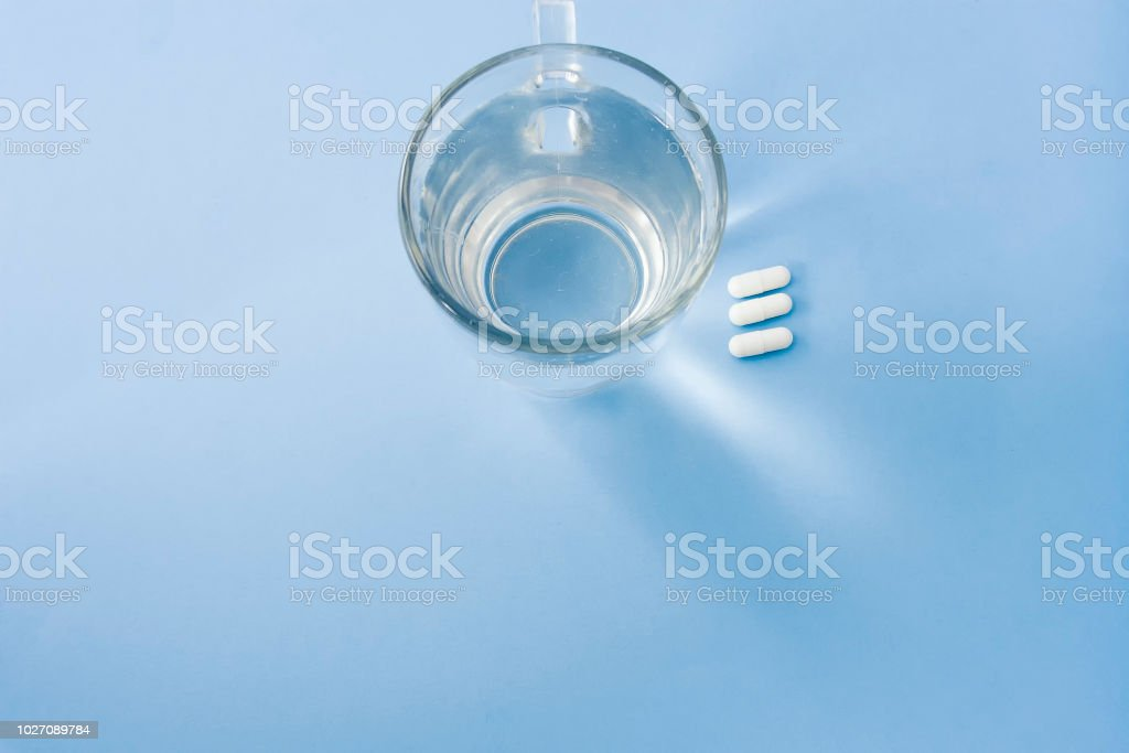 Organized white pills with a cup of fresh water stock photo