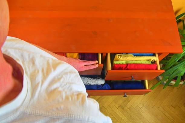 Organizing and cleaning home. Man preparing orderly folded T-shirts in drawer. Man choosing orderly folded T-Shirts in drawer. Man tiding the clothes. Preparing the clothes. The order in chest of drawers. stock photo