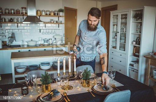 Young men celebrating Christmas at home and prepare Christmas table. Home is decorated with Christmas ornaments and lights.