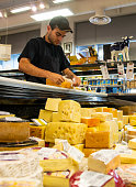 A young employee organizing a gourmet cheese display.