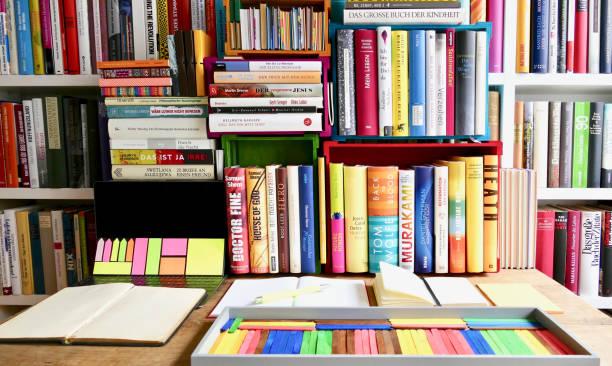 organisieren der bibliothek: tisch und kleine regale im vordergrund, mehr regale und bücher im hintergrund - deutsche bibliothek stock-fotos und bilder