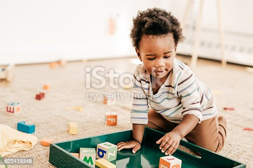 Toddler putting together all toy blocks on the special green trayNominated for S+