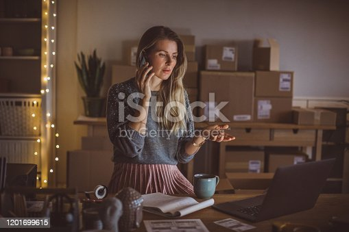 Working woman at online shop. She wearing casual clothing and using mobile phone for communication with customer