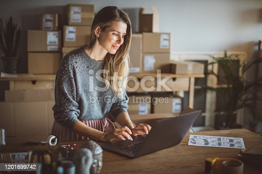Working woman at online shop. She wearing casual clothing and using laptop for work organization