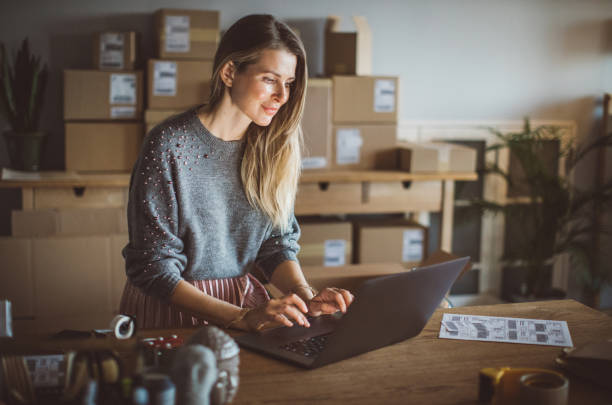 Organizing work in delivery business Working woman at online shop. She wearing casual clothing and using laptop for work organization market vendor stock pictures, royalty-free photos & images