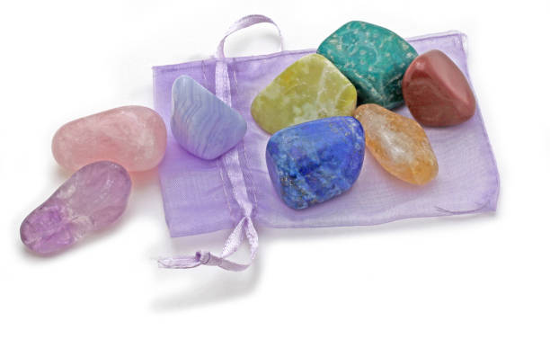 Organza Pouch with Chakra Crystal Set Chakra Crystal Set of eight rainbow colored stones placed on a lilac organza pouch on a white background crystal healing stock pictures, royalty-free photos & images