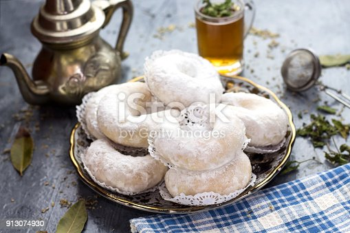 istock Oriental Algerian sweet cookies( kaab el ghazal), tea cup and pot  and mint leaves 913074930