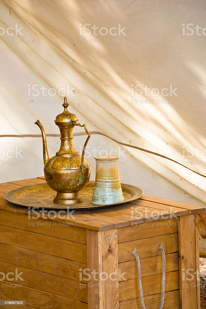 Oriental antique brass teapot with a stoneware cup stock photo