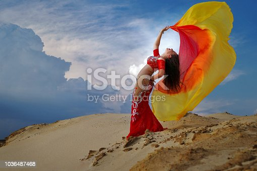 Oriental Beauty dancing sensual belly dance outdoors. Arab dance of seduction. The girl is holding a shawl in her hands.