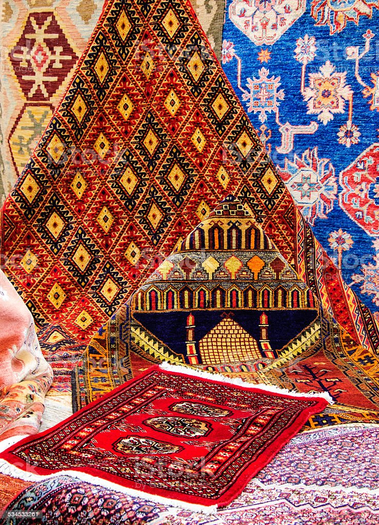 Oriental carpets in market. Mosque image on one of  rugs. stock photo