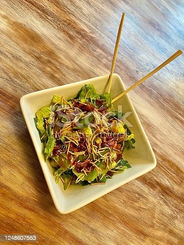 Big bowl of oriental chef salad with teriyaki chicken, mandarin oranges, lettuce and chow mein noodles.