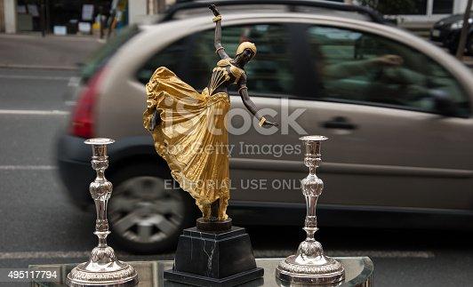 Paris, France - March 10, 2013: Oriental dancer figurine at Beaumarchais flea market and the street at background. Beaumarchais flea market serves the professional antique dealers.