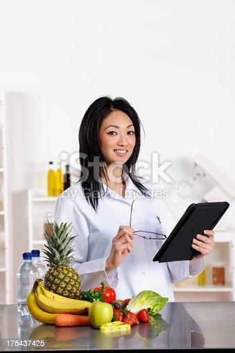 istock Oriental Healthcare Professional Using Digital Tablet 175437425