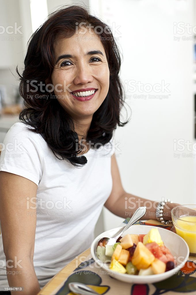 Oriental Housewife Having Fruit for Breakfast stock photo